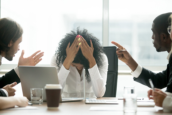 Woman sitting at a desk with her head in her hands being shouted at by a colleague