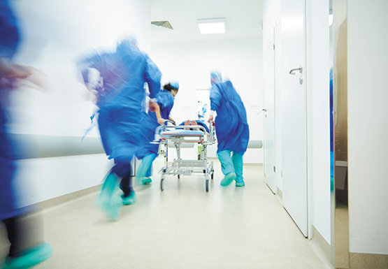 Emergency staff wheel patient quickly through a hospital corridor