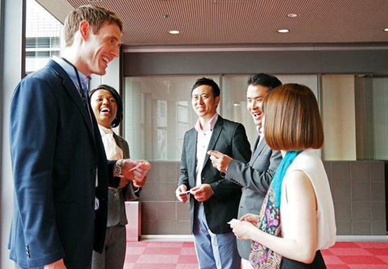 Group of smiling male and female managers exchanging business cards