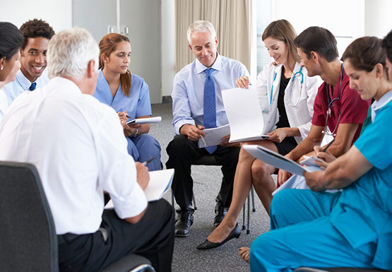 Group of senior clinical staff sat in a circle
