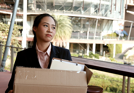 Woman leaving workplace with her belongings in a cardboard box