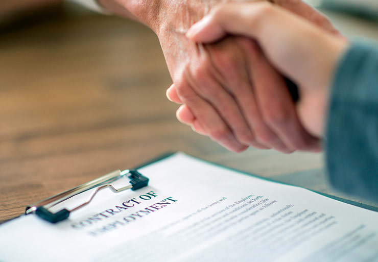 Shaking hands over a contract on a desk