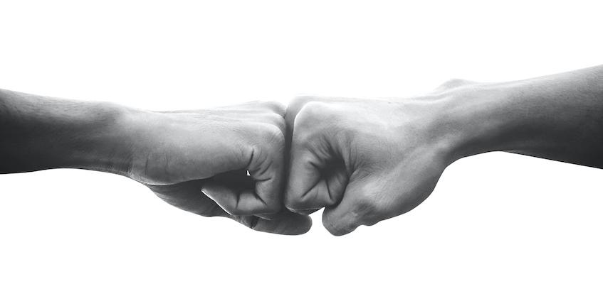 Black and white allies fist bump