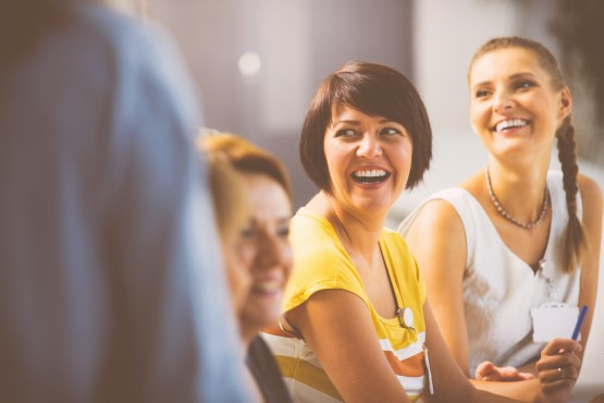 Group of women smiling at a meeting